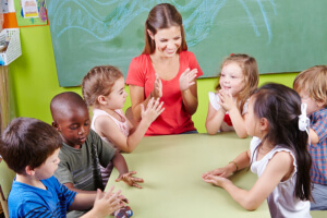 teacher and her students clapping hands